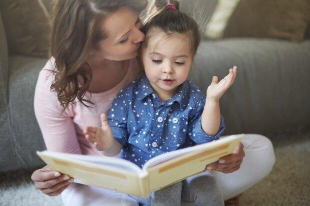 Eine Mutter liest ihrer kleinen Tochter ein Buch vor