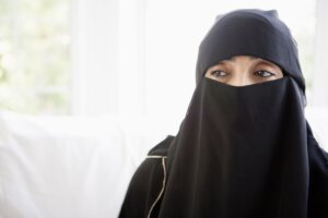 Frau trägt Burka vor einem hellen Hintergrund