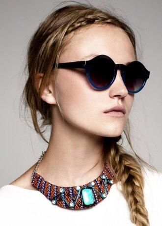 Junges Model mit Sonnenbrille und Zopf