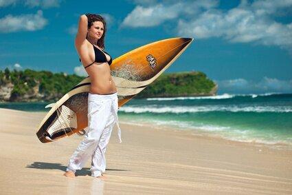 Frau mit Surfboard am Strand von Fuerteventura