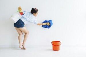 Frau putzt Wand