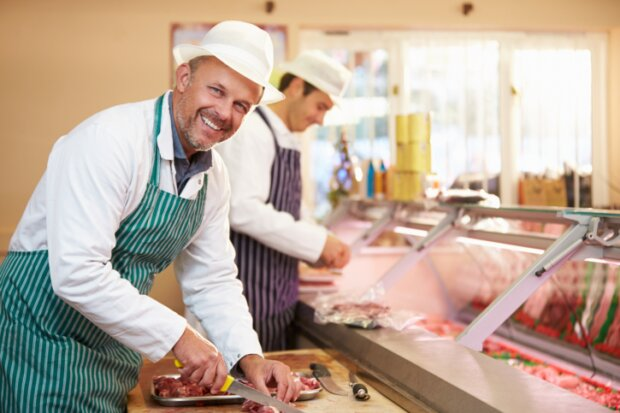 Zwei Männer schneiden Fleisch in der Metzgerei
