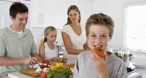 Mutter, Vater und zwei Kinder kochen gemeinsam in der Küche