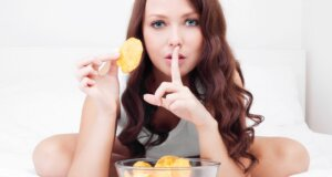 Junge Frau isst Chips im Bett - Heißhunger