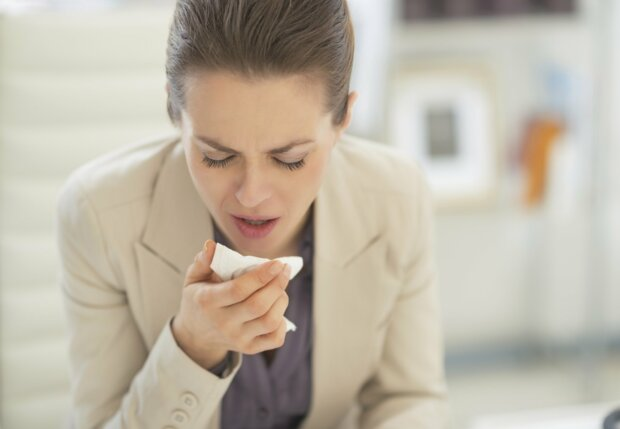 Frau niest in Taschentuch